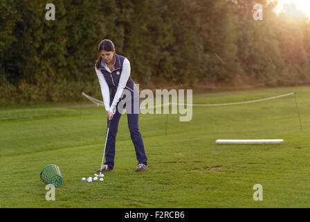Female golfer standing on the driving range on a late afternoon day, concentrating for the next swing - Stock Photo