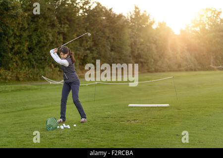 Female golfer standing on the driving range on a late afternoon day, concentrating while swining her club - Stock Photo