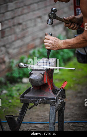A farrier hard at work re shoeing horses - Stock Photo
