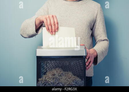 a man is shredding a piece of paper - Stock Photo
