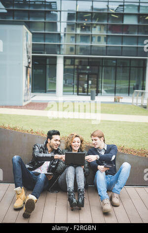 Multiracial business people working outdoor sitting on the ground, connected with technological devices like tablet - Stock Photo