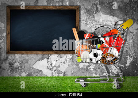 shopping cart filled with sports equipment in front of stone wall with blackboard - Stock Photo