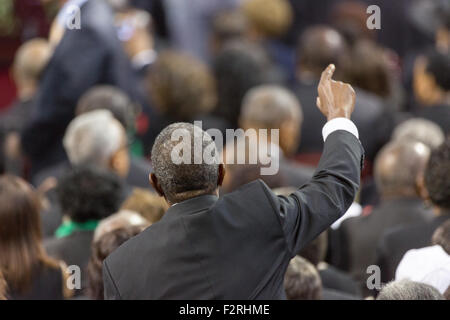 A mourner stands for a hymn during the funeral of slain State Senator Clementa Pinckney at the TD Arena June 24, - Stock Photo