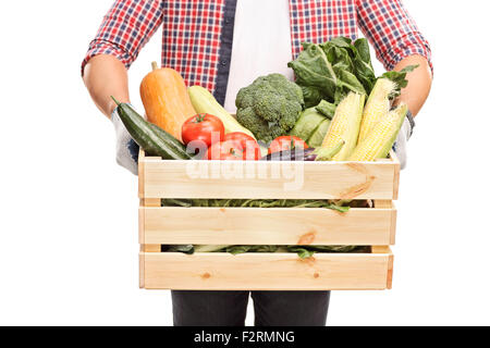 Close-up on a man holding a wooden crate full of fresh vegetables isolated on white background - Stock Photo