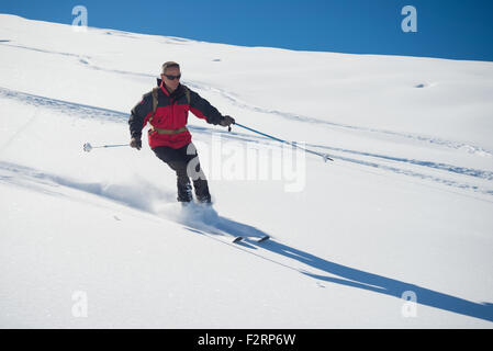 One person skiing downhills off piste on snowy slope in the italian Alps, with bright sunny day of winter season. - Stock Photo