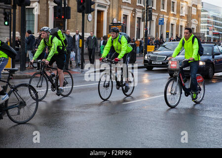 Cyclists wearing high-visibility clothing riding in London - Stock Photo