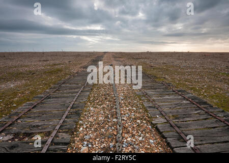 Wooden tracks and pulley chain leading to vanishing point on shingle beach at Rye Harbour Nature Reserve, East Sussex, - Stock Photo