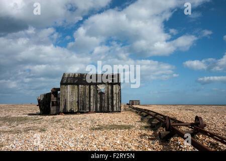 Abandoned old fishing hut and rail track on the shingle beach at Dungeness, Kent, England, UK - Stock Photo
