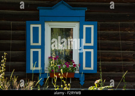 Wooden House with a Blue Window - Stock Photo
