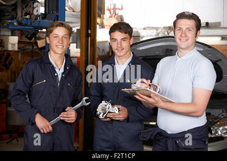 Mechanic Teaching Trainees In Garage Workshop - Stock Photo