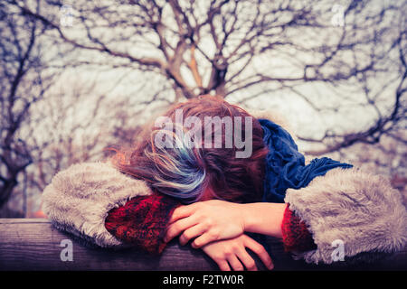 A Young woman is leaning on a wooden beam in the park - Stock Photo