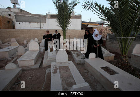 Sept. 24, 2015 - Nablus, West Bank, Palestinian Territory - Palestinian women pray over the graves of relatives - Stock Photo