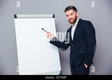 Portrait of a happy businessman presenting something on blank board over gray background - Stock Photo