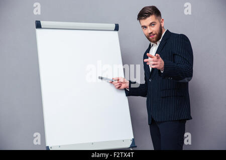 Portrait of a confident businessman presenting something on blank board over gray background - Stock Photo