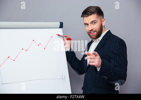 Portrait of a happy businessman presenting something on board over gray background - Stock Photo