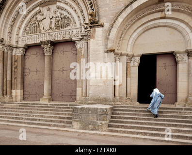 A nun holds her hood in the wind as she hurries across the square in front of the Abbey of Vézelay, the Basilica - Stock Photo