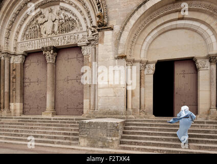 A nun holds her hood in the wind as she hurries up the steps of the Abbey of Vézelay, the Basilica of St Magdelene - Stock Photo