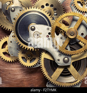 Metal collage of clockwork gears on copper background - Stock Photo