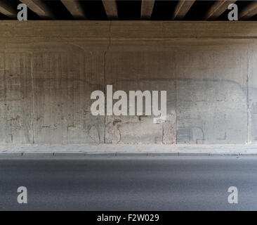 Concrete wall and asphalt road under the bridge. - Stock Photo