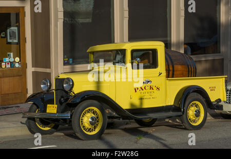 Asheville North Carolina Pack Square with yellow old historic truck at Pack's Tavern in vintage building - Stock Photo