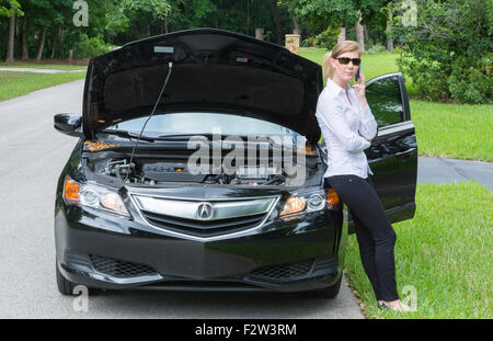 Young woman with car broken down on side of road using cell phone to call for help and being rather annoyed MR Model - Stock Photo