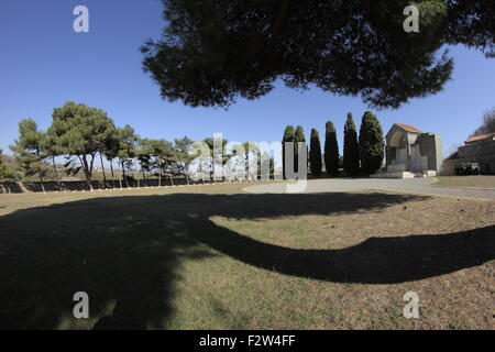 The Great cross cove surrounded by cypress trees & gravel corridor, overshadowed by a tree. CWGC Portianos cemetery. - Stock Photo