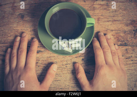 A man is resting his hands on a table with a cup of coffee and some pills - Stock Photo