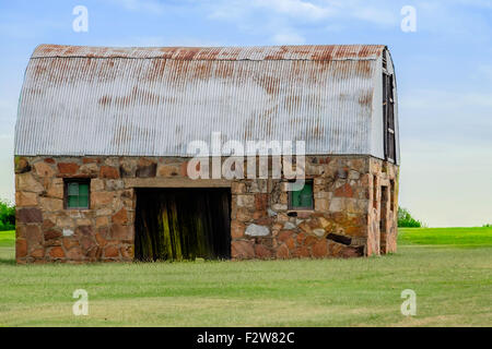 An old rustic stone barn with a rusty tin roof in the Oklahoma, USA countryside. - Stock Photo