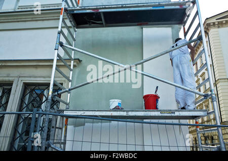man on scaffolds restructuring a house - Stock Photo
