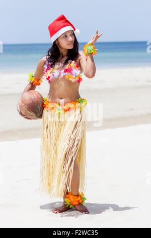 Hawaii hula dancer with coconut posing on the beach - Stock Photo
