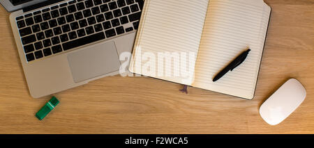 Laptop and opened a notebook with a pen lying on a wooden surface. - Stock Photo
