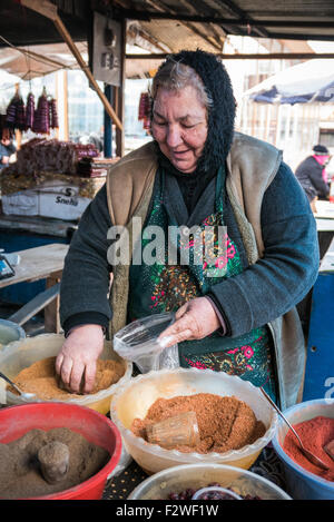 A female market trader selling spices on her stall in Tbilisi, Georgia. - Stock Photo