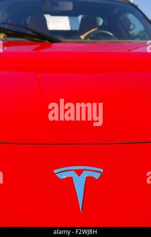 Logo of Tesla Motors on the bonnet of a red Tesla electric car - Stock Photo