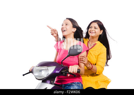 2 indian mother and young daughter Scooty Riding enjoy finger pointing showng - Stock Photo