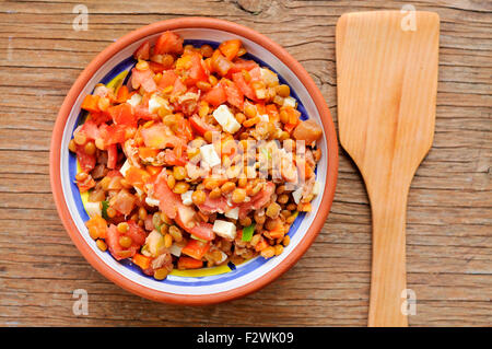 high-angle shot of a earthenware bowl with a lentil salad on a rustic wooden table - Stock Photo
