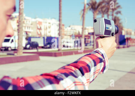 closeup of a young man wearing a red plaid shirt points a retro film camera like it was a gun, in a urban scenery - Stock Photo