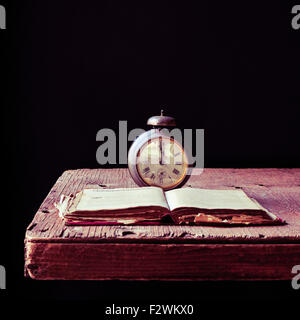 an old alarm clock and an open old book on a rustic wooden table, against a black background - Stock Photo