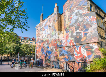 A bicycle tour  people viewing the The Battle of Cable Street mural shadwell Cable street London England UK GB EU - Stock Photo
