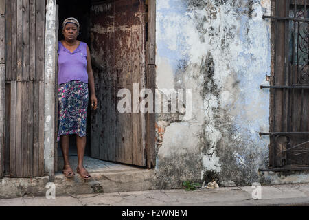 A Cuban woman stands on the threshold of her property on Cuba street, central Havana. - Stock Photo