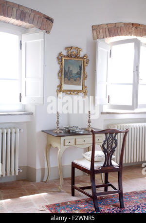 Gilt framed picture above small antique dressing table with silver candlesticks and antique chair in Italian bedroom - Stock Photo