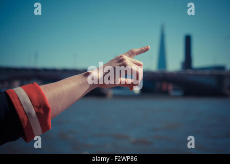 A woman's hand is pointing at a skyscraper by the river - Stock Photo