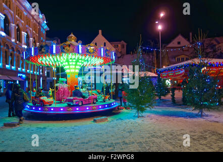 RIGA, LATVIA - DECEMBER 28, 2014: Little kids riding a merry-go-round at the traditional Christmas market in the - Stock Photo