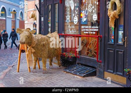 RIGA, LATVIA - DECEMBER 28, 2014: Little straw bull figure at the entrance to a restaurant in Old Riga (Latvia) - Stock Photo