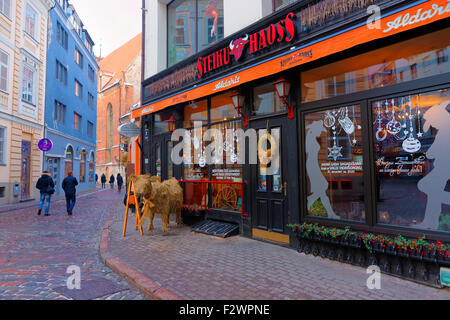 RIGA, LATVIA - DECEMBER 28, 2014: Steak house in Old Riga (Latvia) decorated for Christmas with a little straw bull - Stock Photo