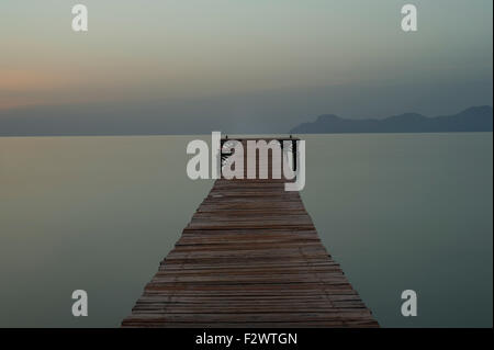 The wooden jetty at sunrise looking over the bay in Port d'Alcudia, Mallorca - Stock Photo