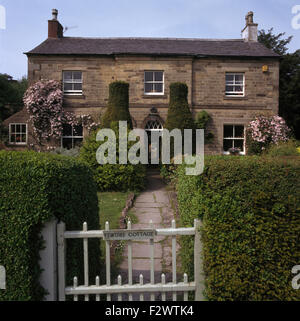 Paved path leading to traditional country house with tall clipped yews on either side of front door - Stock Photo