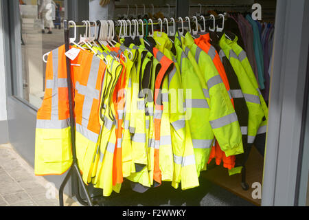 'Hi-vis' (High visibility) jackets for sale on rack in shop doorway in Bedford, Bedfordrshire, England - Stock Photo