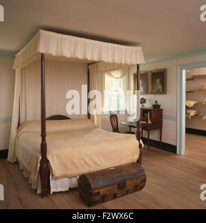 Cream drapes and linen on four poster bed in country bedroom with an antique chest and wooden flooring - Stock Photo
