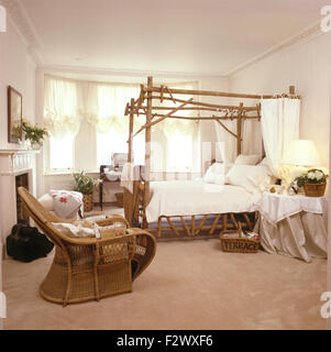 Cane chair in nineties bedroom with rustic wooden four poster bed with white drapes and linen - Stock Photo