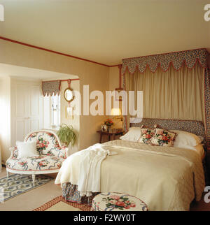 Patterned lambrequin pelmet above bed with rose patterned cushions and cream quilt in nineties bedroom - Stock Photo